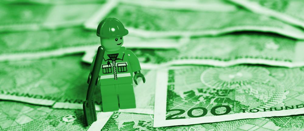 Legofigur i arbeidsklær stående på tohundrelapper med grønt filter over. Foto.