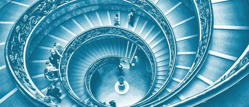 Spiraltrapp over flere etasjer sett ovenifra. Flere personer står i trappa. Bilde.