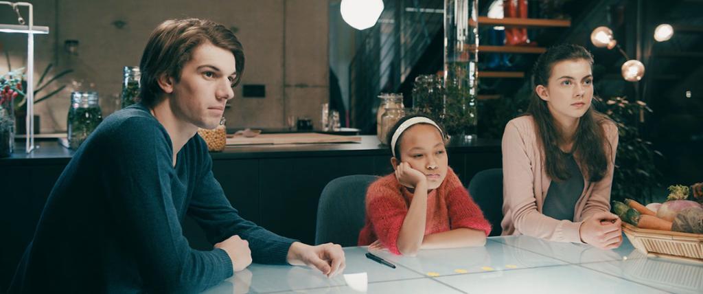 Tre unge ved et bord. Foto.
