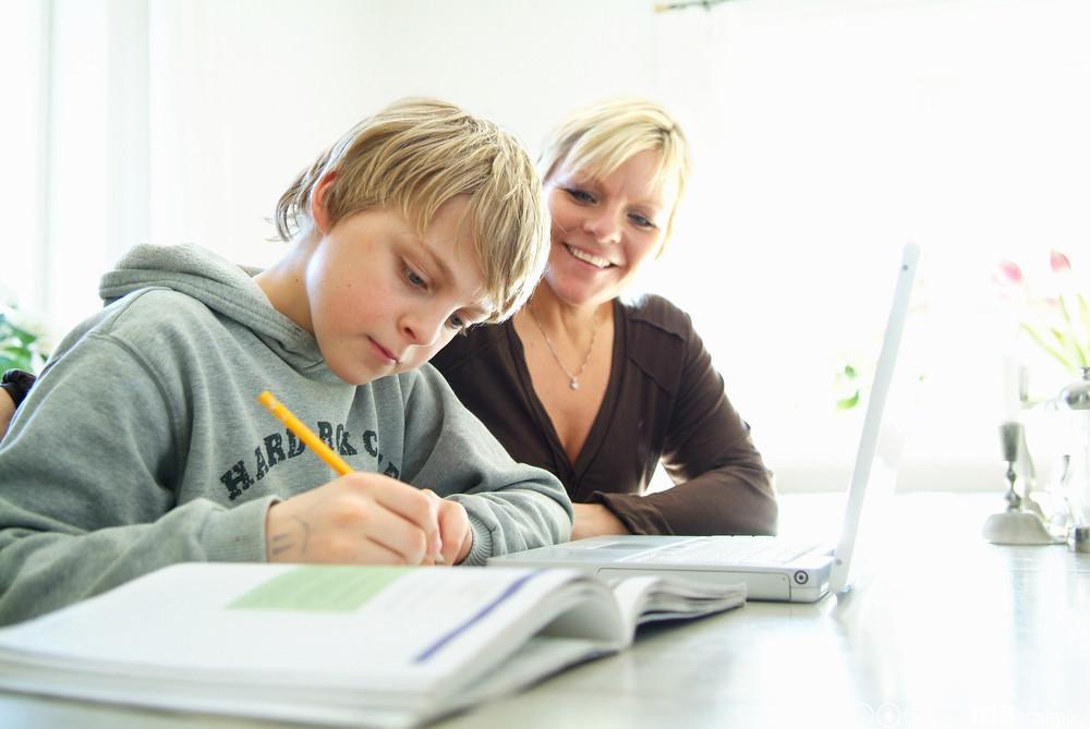 Gutt får hjelp til skolearbeid av lærer. Foto.