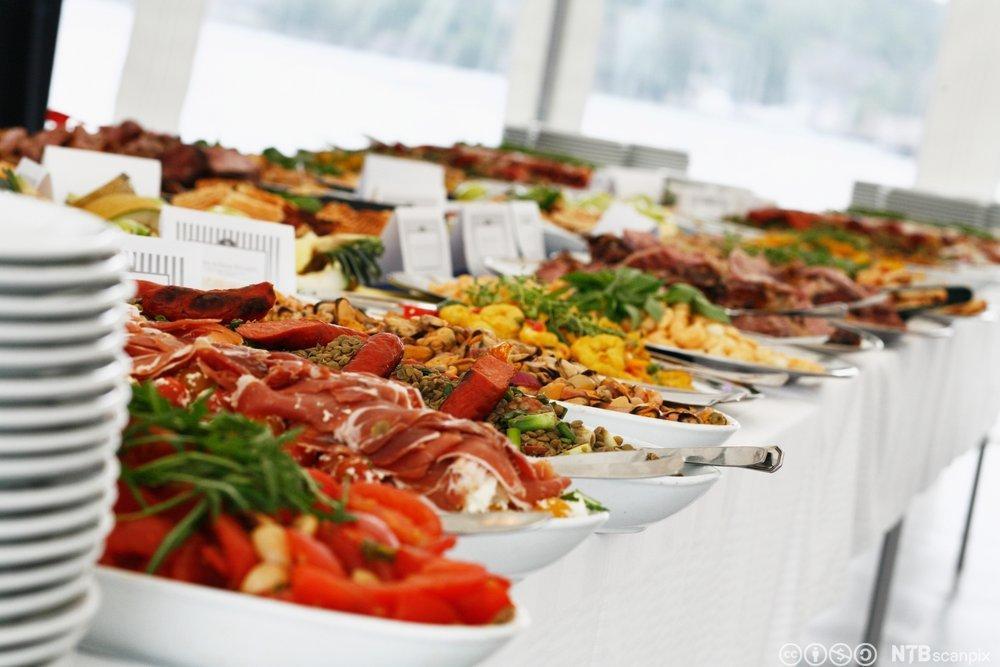 Mange fat med ulike matretter på et koldtbord. Foto.