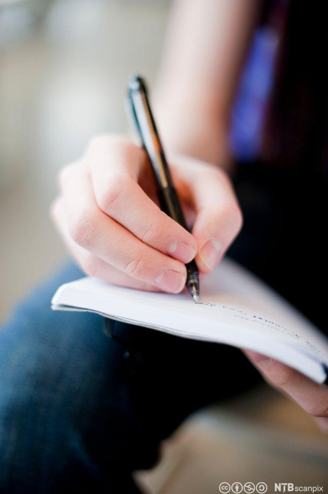 Fingre som skriver i notatbok. Foto.