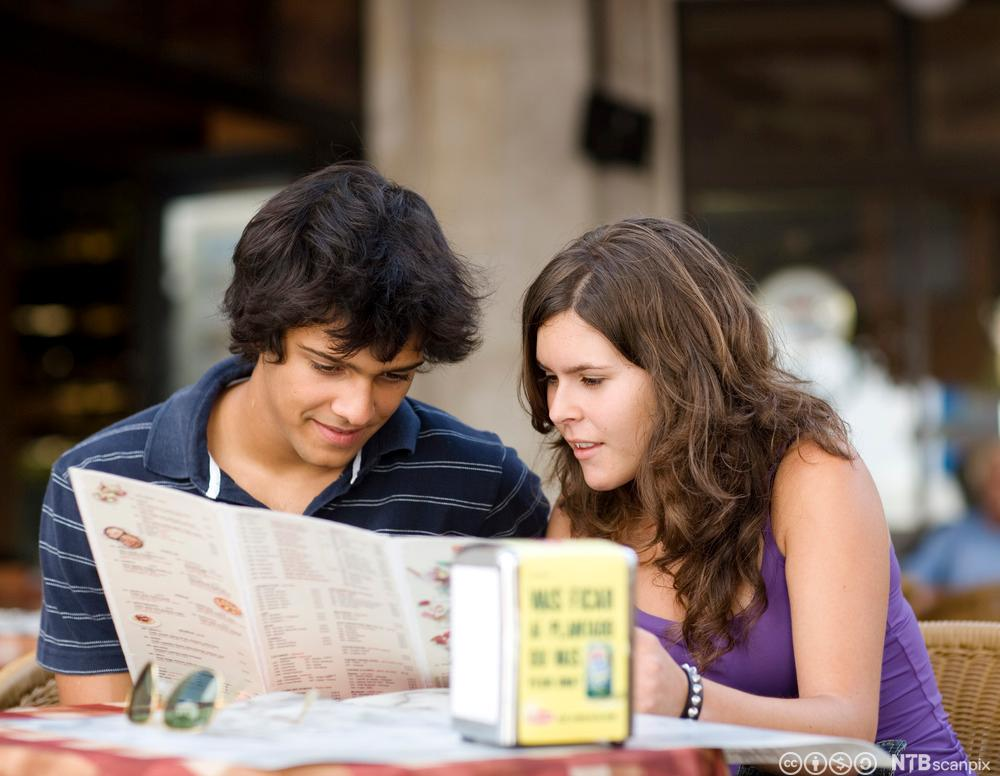 Bilde av et kjærestepar som studerer en meny. Foto.
