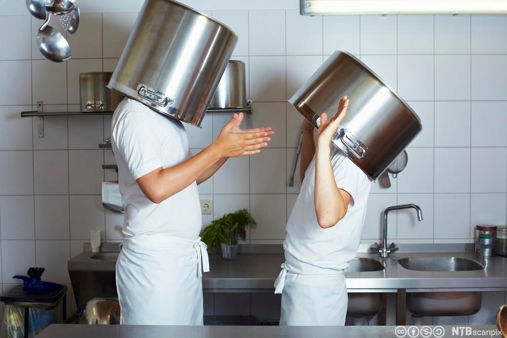 To kokker har dratt en gryte over hvert sitt hode. Foto.
