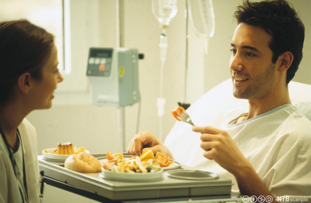 En man sitter i senga og spiser, mens en dame holder han med selskap.Foto