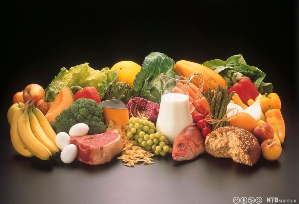 Frukt, grønnsaker, fisk, kjøtt og egg ligger i en haug på et bord. Foto.