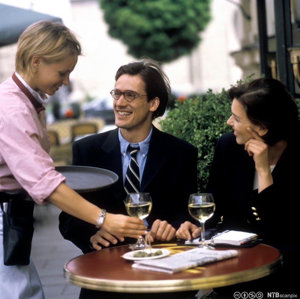 Servitør som serverer gjester vin. Foto.