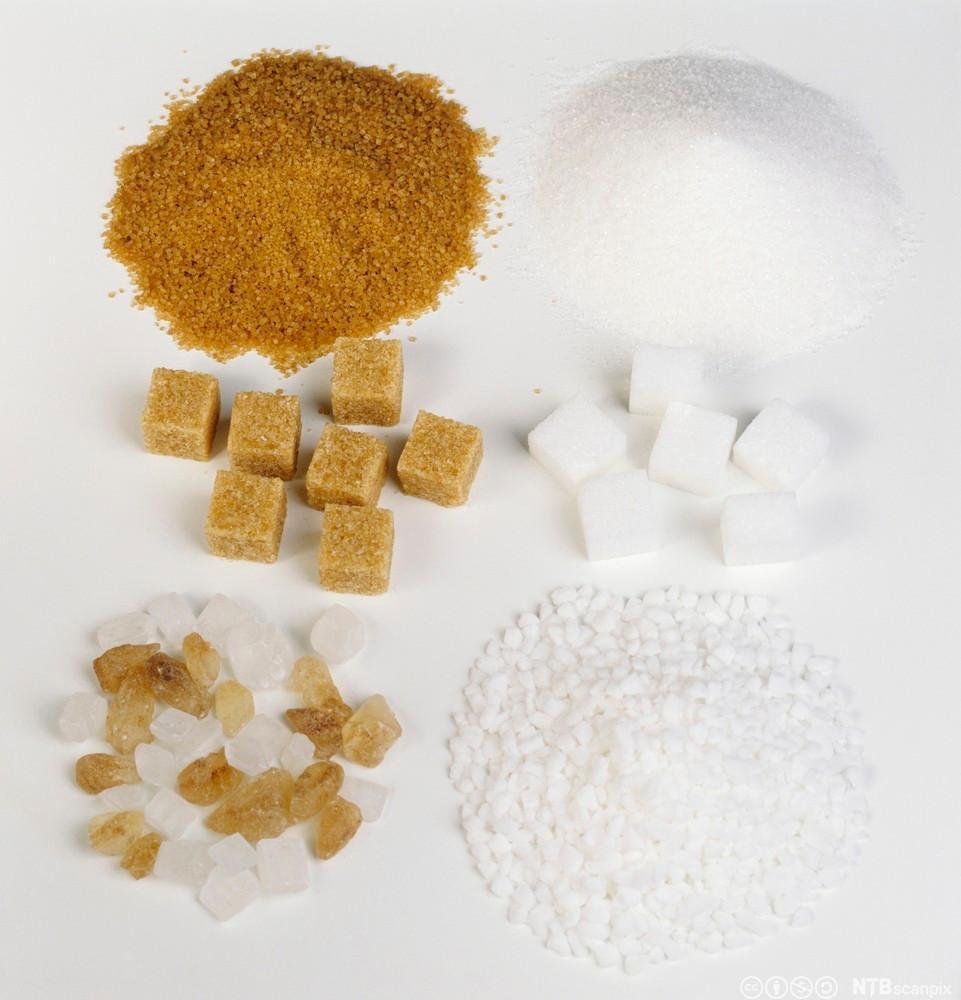 Fleire sukkersortar som ligg i haugar på eit bord. Foto.