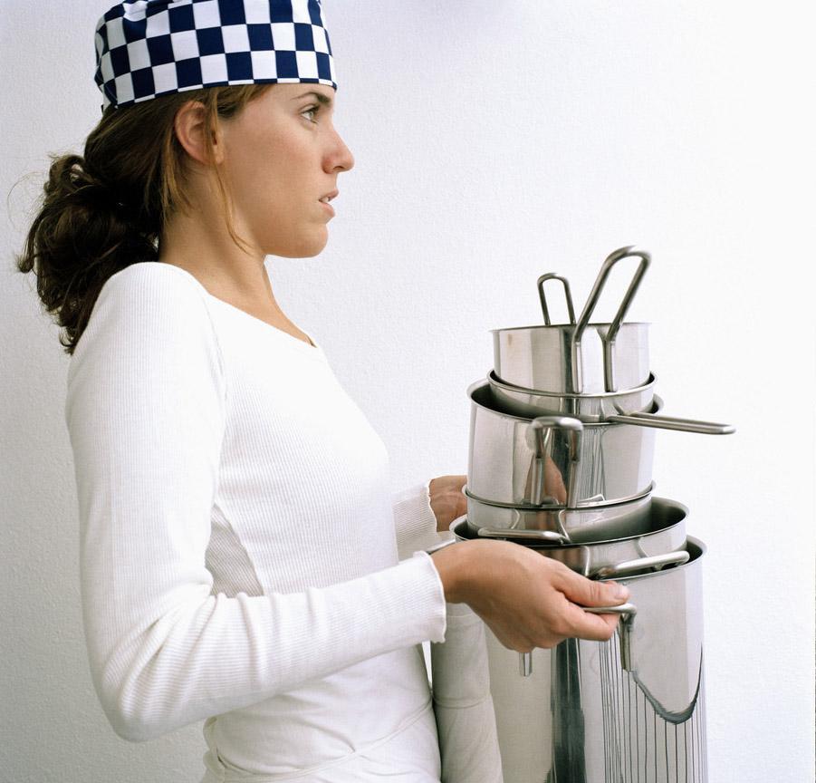 Kvinnelig kokk bærer en stabel med gryter. Foto.