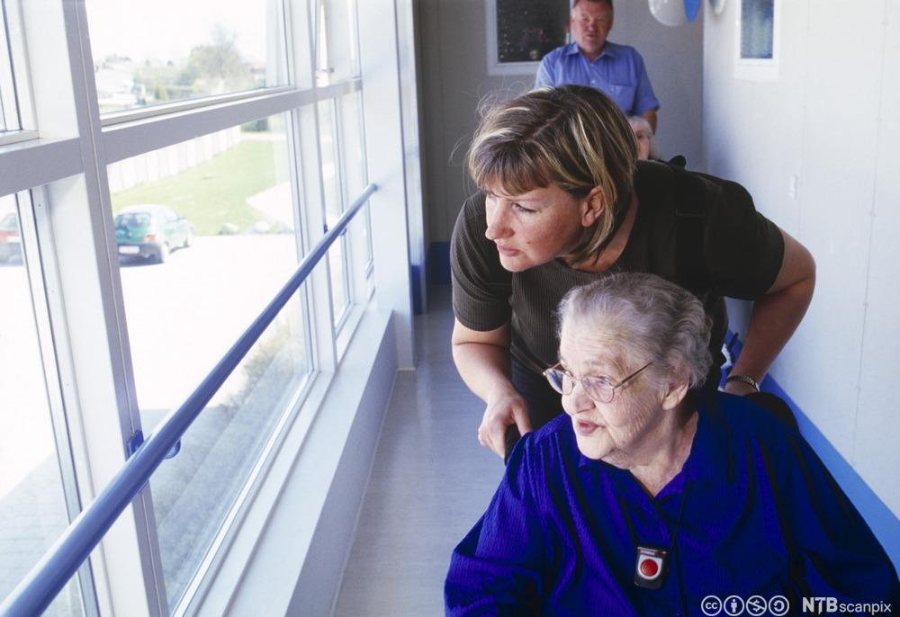 Eldre dame i rullestol og en pleier ser ut av vinduet. Foto.