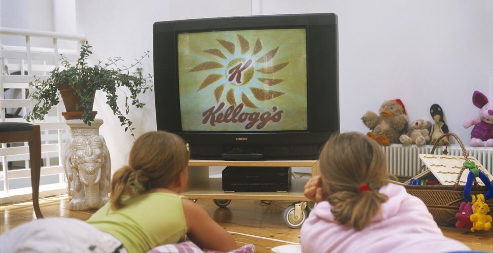 To jenter ligger på gulvet og ser på TV. Foto.