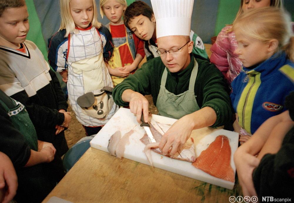 Kokk viser barn hvordan man renser fisk