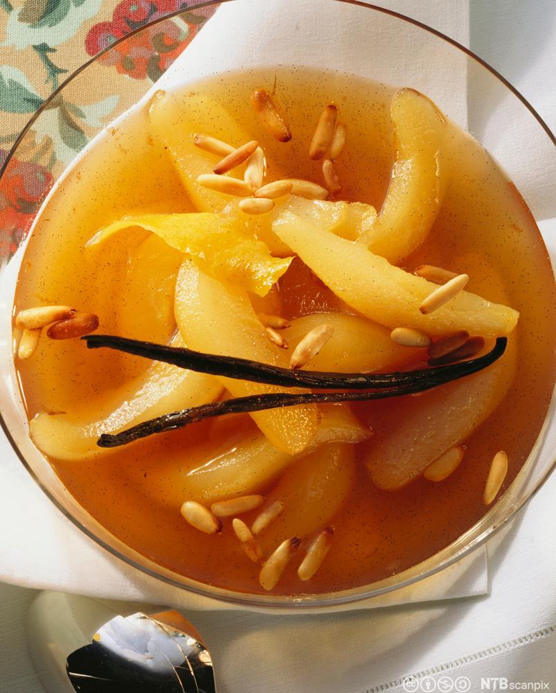 Pærekompott med pinjekjerner i en skål. Foto.