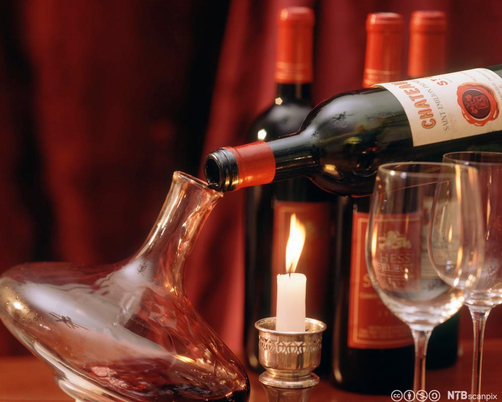 Ei vinflaske blir dekantert, det vil seie at vinen blir helt forsiktig over i ein karaffel. Foto.