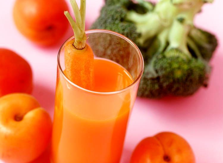 Bilde av et glass med gulrotjuice, brokkoli og frukt