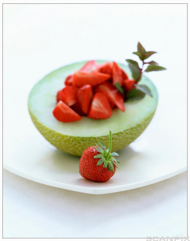 Ein melon som er delt i to og fylt med jordbær. Foto.