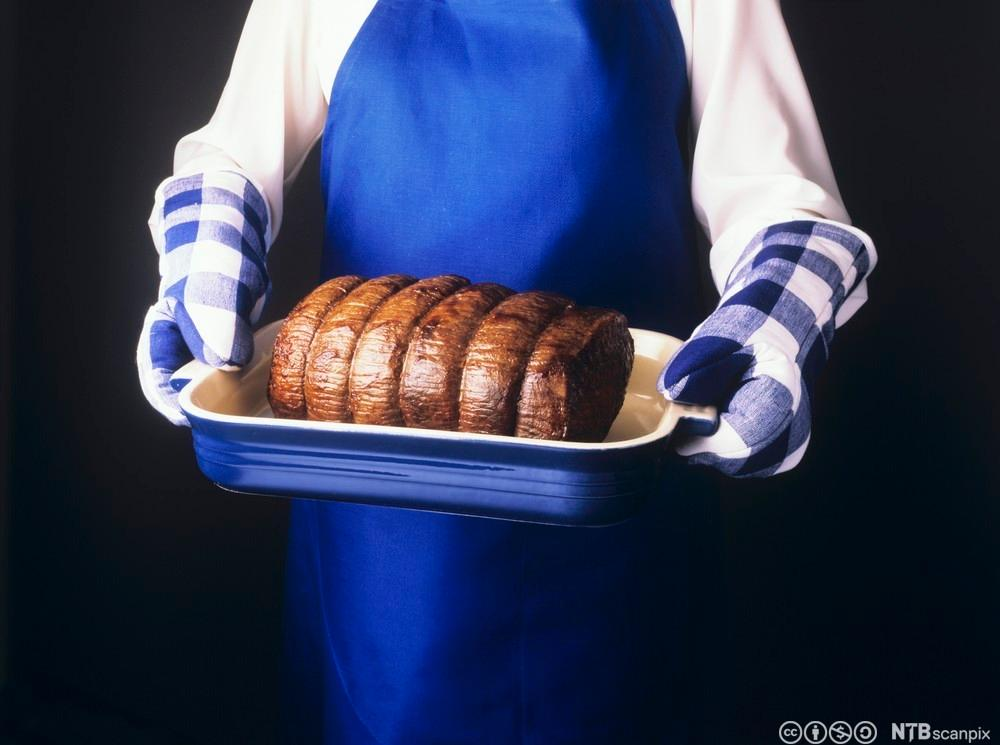 En hanskekledd kokk holder en varm form med roastbeef. Foto.