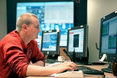 Ung mann sitter foran stasjonær PC. Foto.