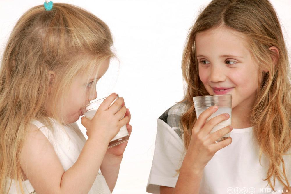 To jenter som drikk mjølk. Foto