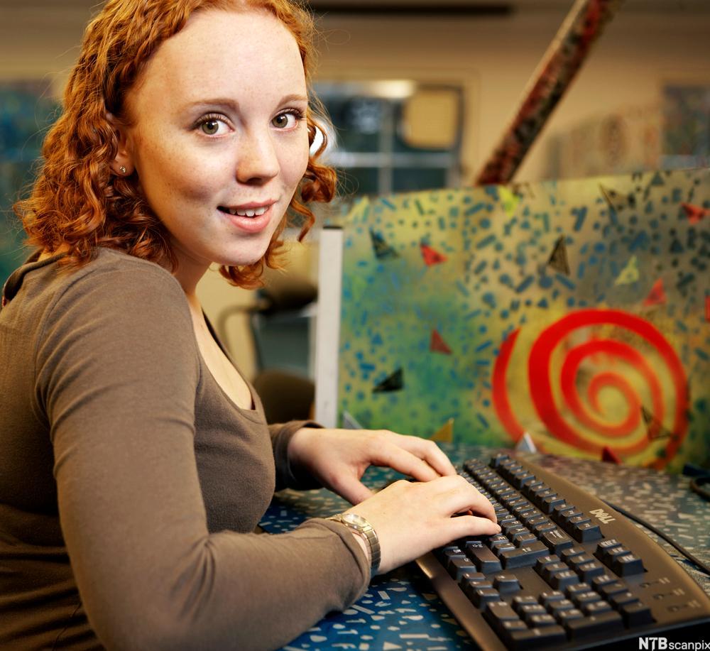Jente som skriver på tastatur. Foto.