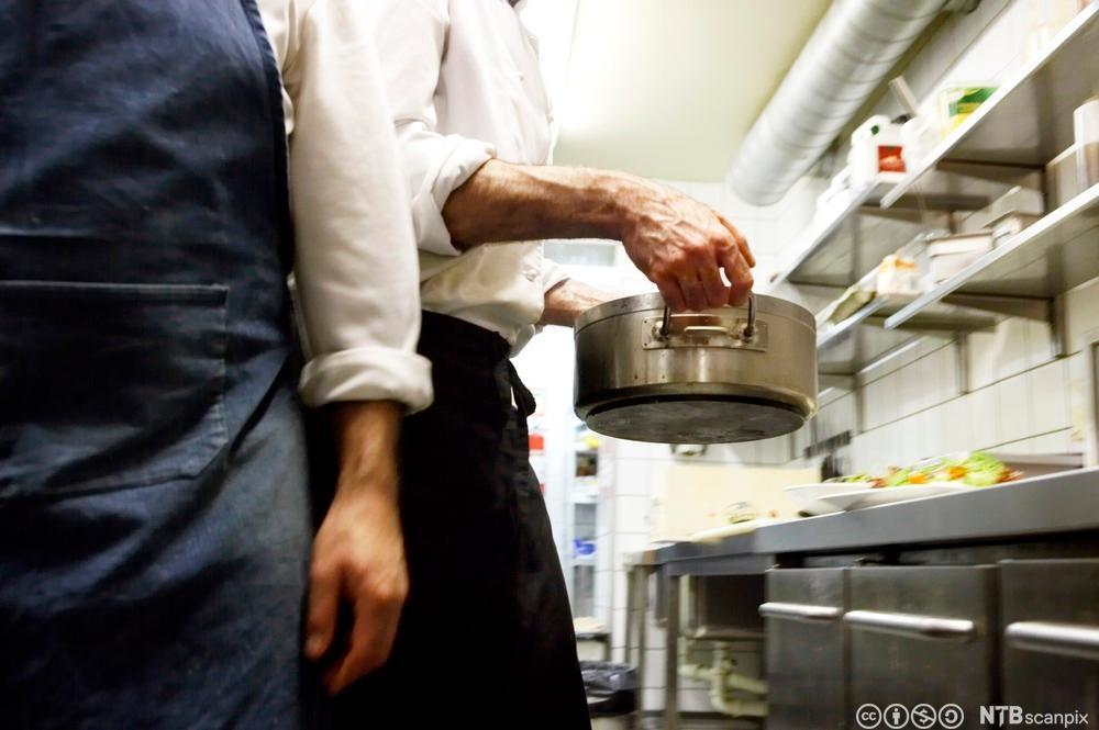 To kokker på et kjøkken som arbeider. Foto.