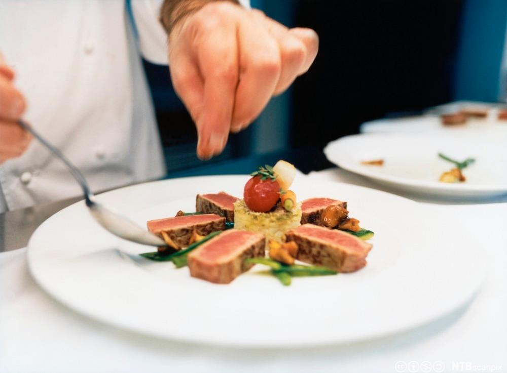 Kokk som legg opp mat på ein tallerken. Foto.
