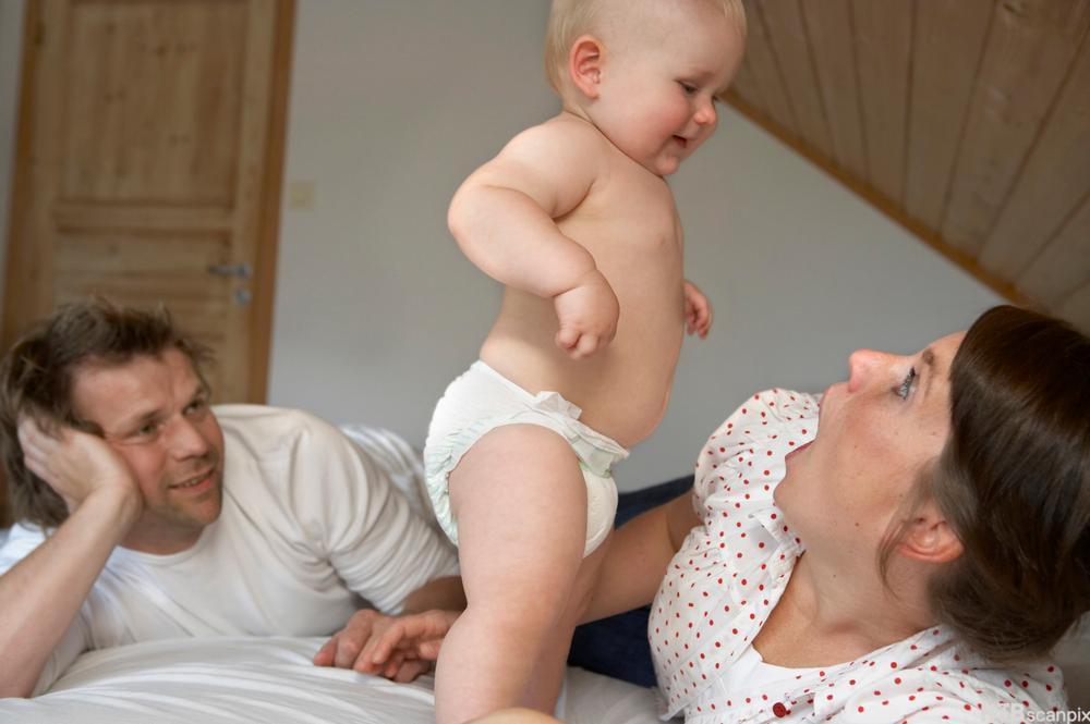 Foreldre og barn i ei seng. Bilde.