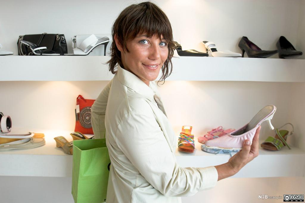 Kvinne ser på sko i en skobutikk. Foto.