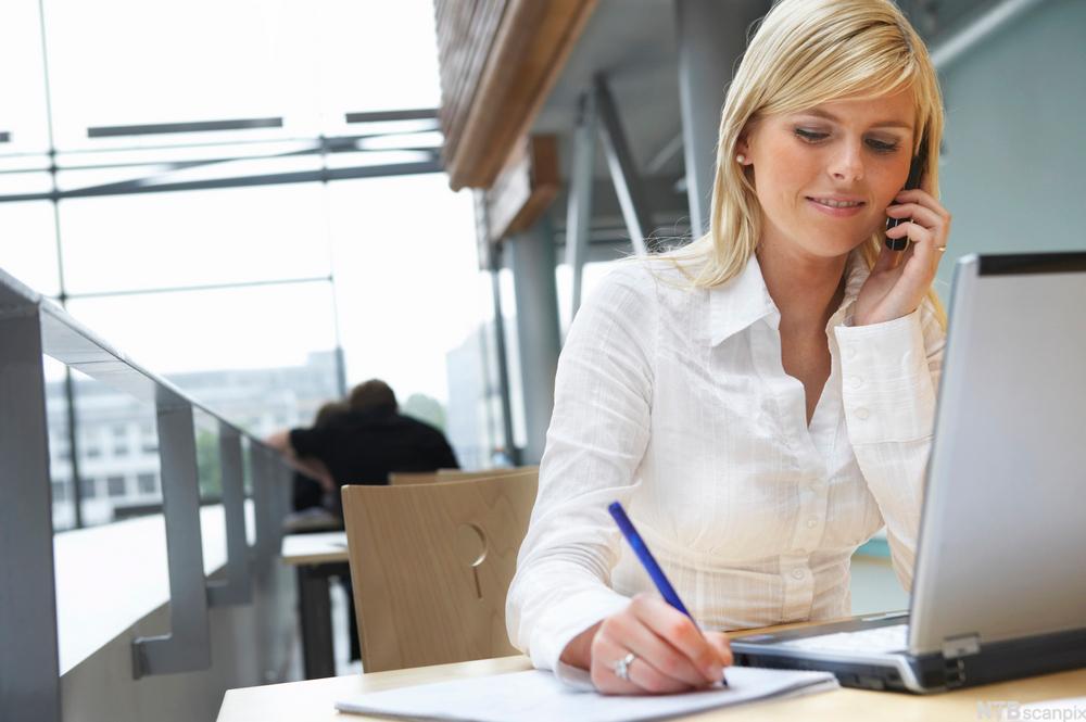 Kvinne som sitter foran en datamaskin og samtidig skriver på et ark. Foto.