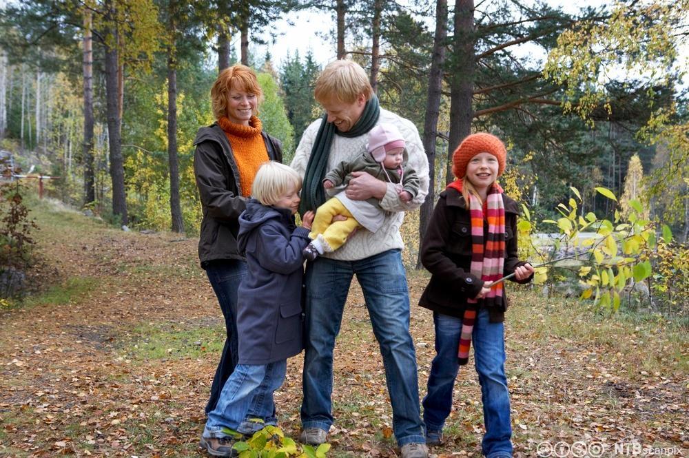 Familie på tur i skogen. Foto.