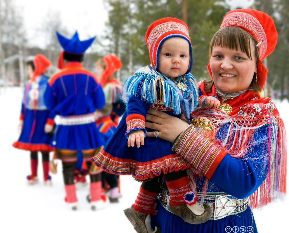 Samisk kvinne bærer et lite barn. Foto.