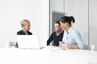 To kvinner og en mann sitter foran en PC og diskuterer. Foto.