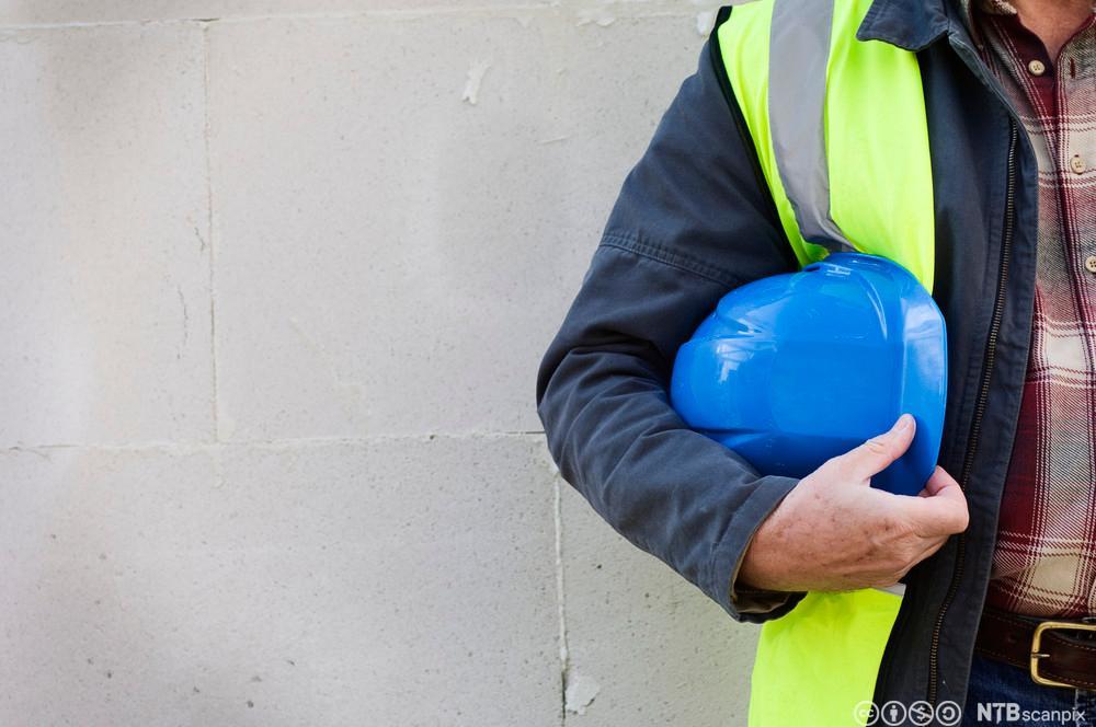 Person med arbeidshjelm under armen. Foto.