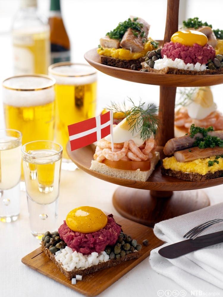 Bilde av danske smørbrød med forskjellig pålegg og øl ved siden av. Foto.