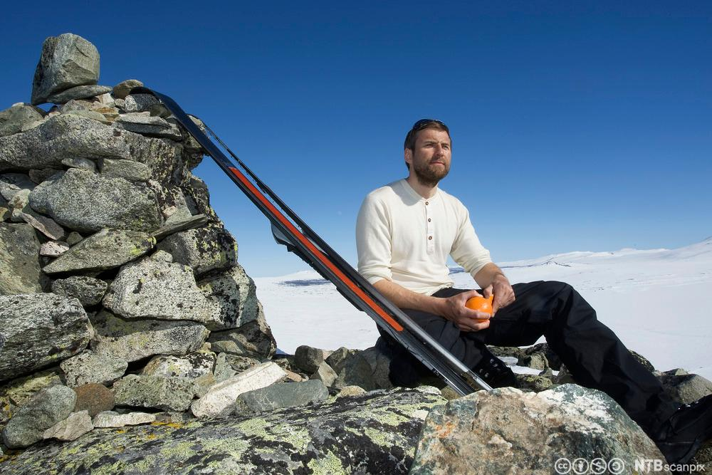 Mann spiser en appelsin på en fjelltopp. Foto.