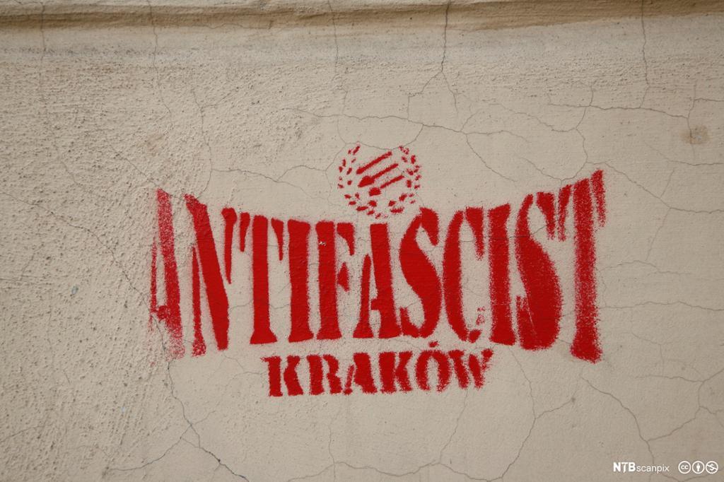 """Rød grafitti på murvegg som sier """"Antifascist Krakow"""". Foto."""