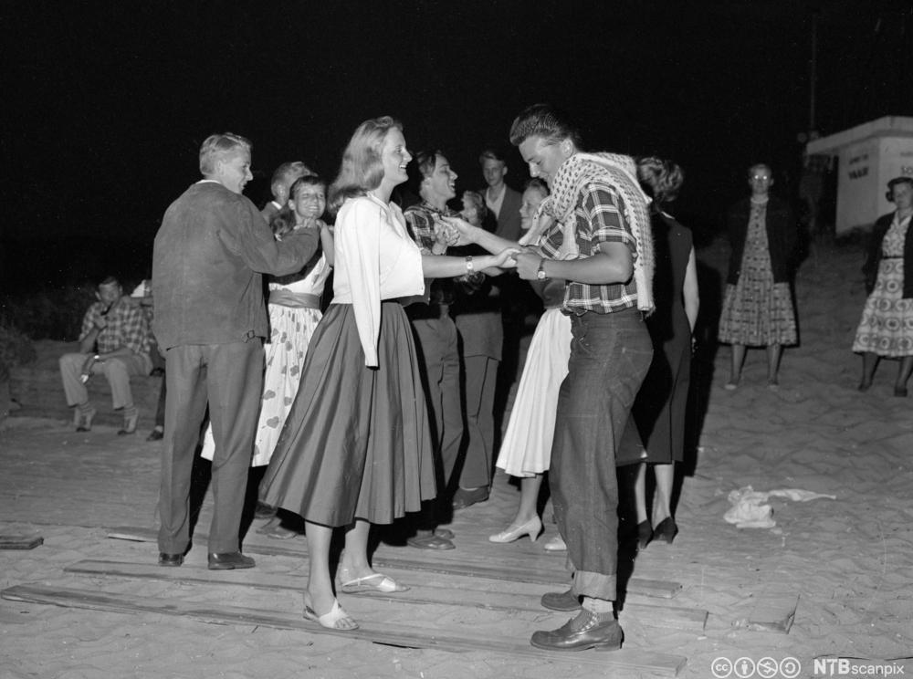 Ungdom kledd i 1950-talls mote danser utenfor et forsamlingshus for unge i 1957. Foto.