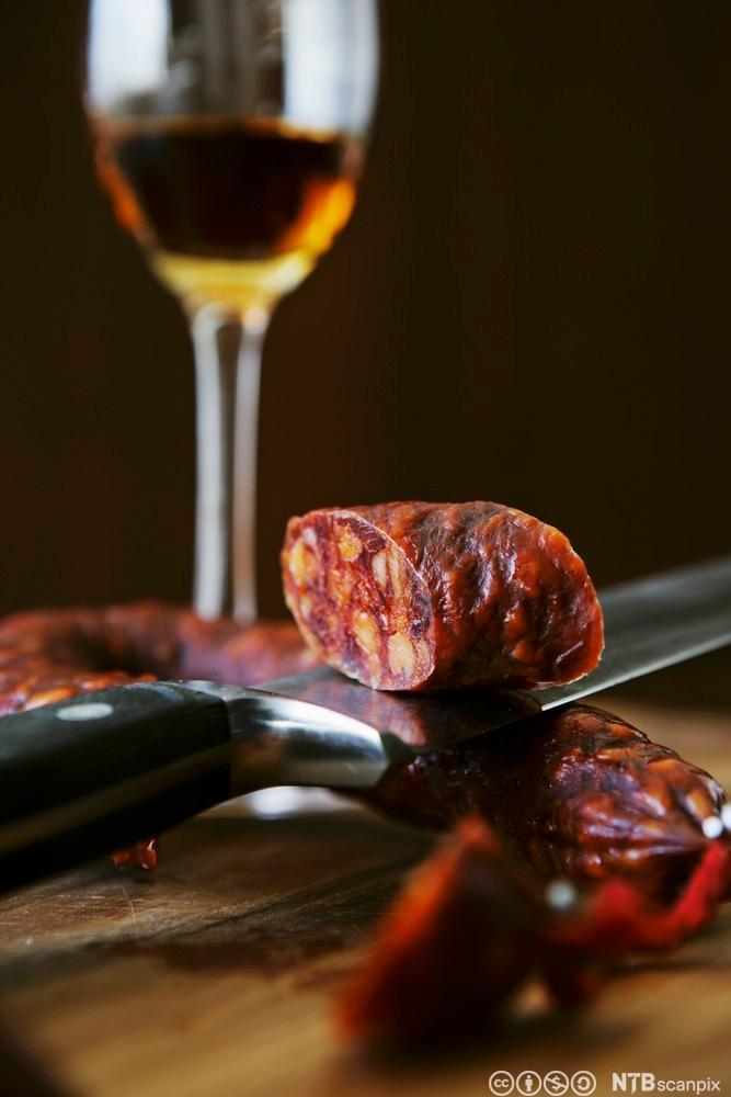 Bilde av en chorizopølse på en kniv, og et glass sherry. Foto.
