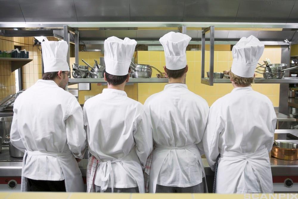 Fire kokker med ryggen mot kamera. Foto.