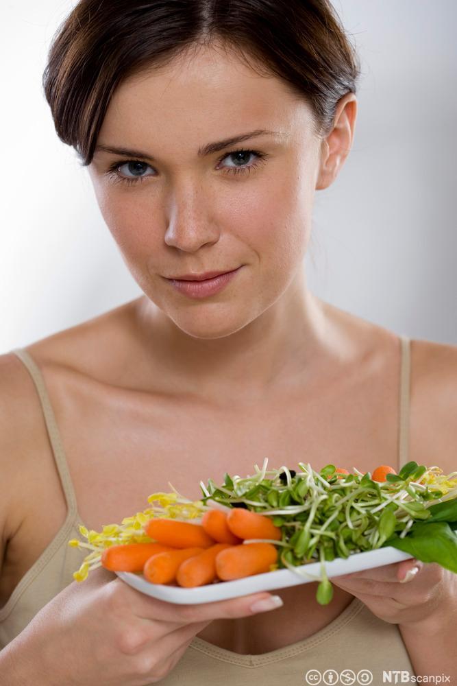 En kvinne holder en tallerken med grønnsaker. Foto.