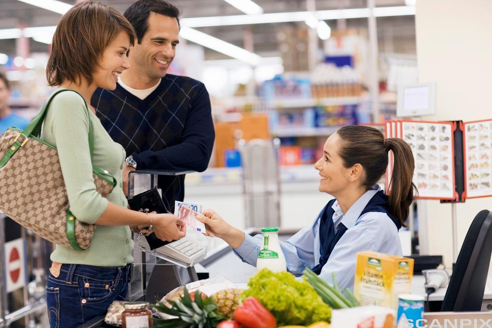 Bilde av en mann og kvinne som betaler for varer i en matvarebutikk.