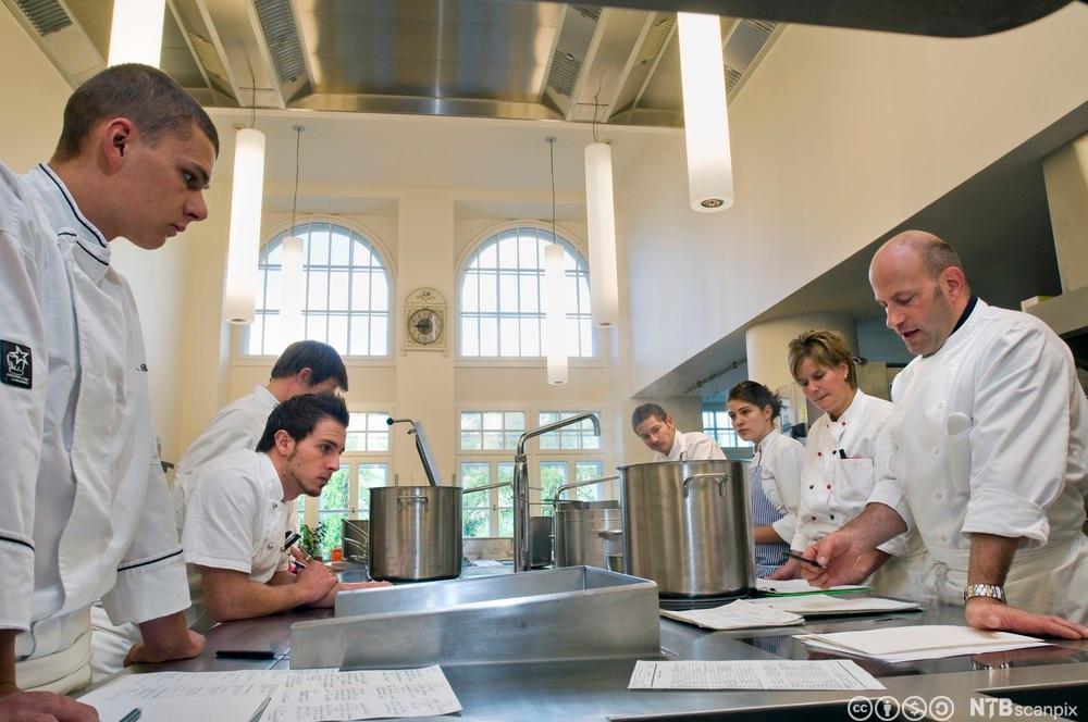 Kokkene på eit kjøkken har møte før service begynner. Foto.