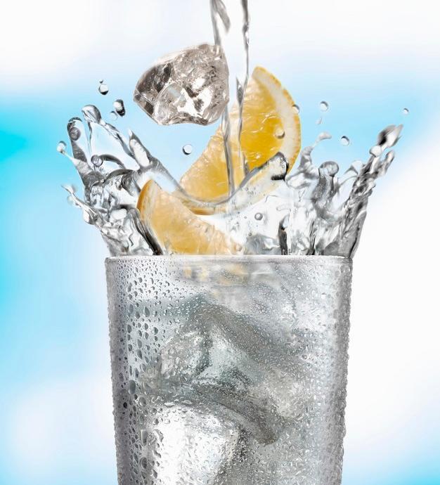 Et glass vann med isbiter og sitron. Foto.