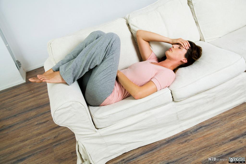 Kvinne med smerter ligger på sofa med en hånd på hode og en hånd på magen. Foto.