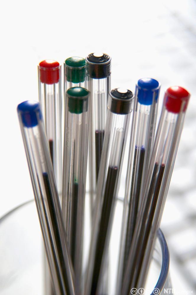 Bic-penner med ulike farge i en kopp. Fotografi.