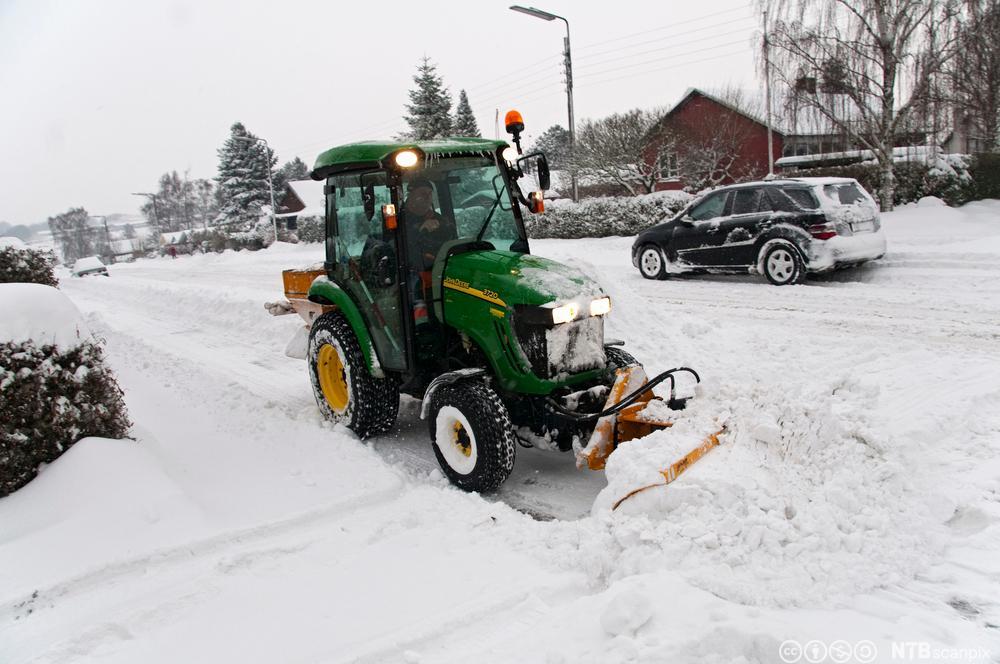 Traktor rydder vekk snø. Foto.