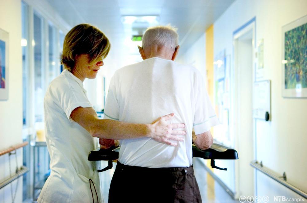Helsefagarbeider hjelper eldre mann på sykehjem. Foto.