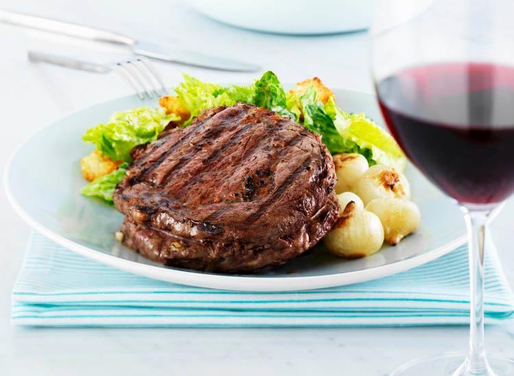 Bilde av en tallerken med et biffstykke og et glass rødvin