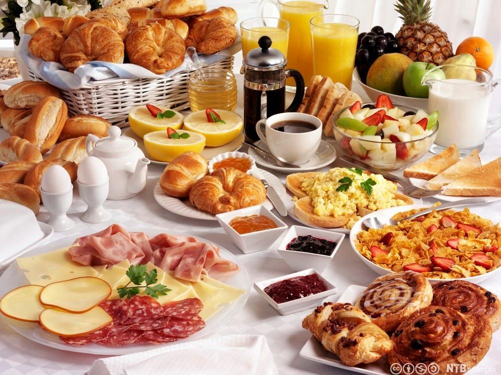 Bilete av eit frukostbord med ulike råvarer til frukost