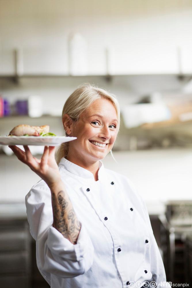 En glad, kvinnelig kokk holder en tallerken klar til servering. Foto.